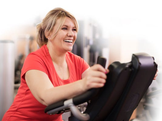 Woman riding on exercise bike at the gym