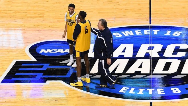 West Virginia Mountaineers head coach Bob Huggins talks with forward Lamont West (15) and guard James Bolden (3).
