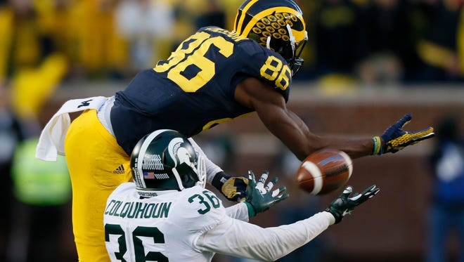 Pass goes through the hands' of Michigan wide receiver Jehu Chesson and Michigan State defender Arjen Colquhoun in the fourth quarter on Saturday.