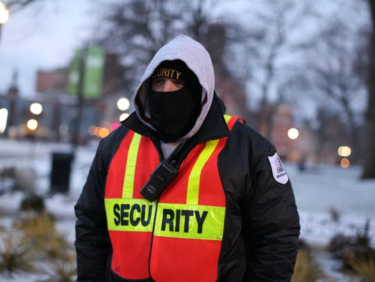 Ryan Strunk, a security guard with NSG Security, stands