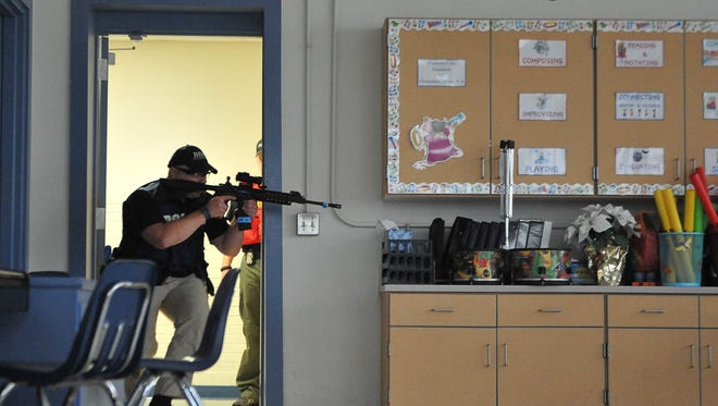 In this file photo, a member of the Ocean View police department clears the area as he participates in a Rescue Task Force Training scenario that has been set up at Lord Baltimore Elementary School in Ocean View. Delaware State Police will be hosting training session in March and April at Sussex high schools.