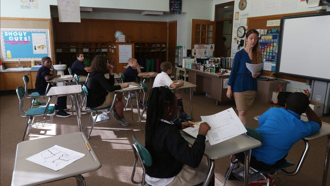 Danielle Lauster, a teacher for this combined third and fifth grade class at Hope Hall, gives the students a spelling assessment quiz.  The Gates school may soon be partnering with the Rochester City School District on special education and alternative education.