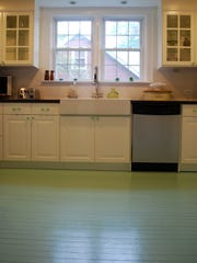 Hardwood kitchen floor designed by Pavone, is painted a soft shade of jade green with a glossy finish, in Westbury, N.Y. The traditional method of painting hardwood floors, rather than staining them, has returned to popularity as homeowners seek inexpensive, fast solutions for scuffed, worn floors.