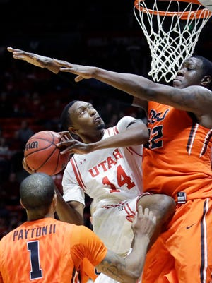 Utah forward Dakarai Tucker, center, goes to the basket as Oregon State's Jarmal Reid, right, defends as Gary Payton II, left, looks on during the second half of an NCAA college basketball game Sunday, Jan. 17, 2016, in Salt Lake City. Utah won 59-53.