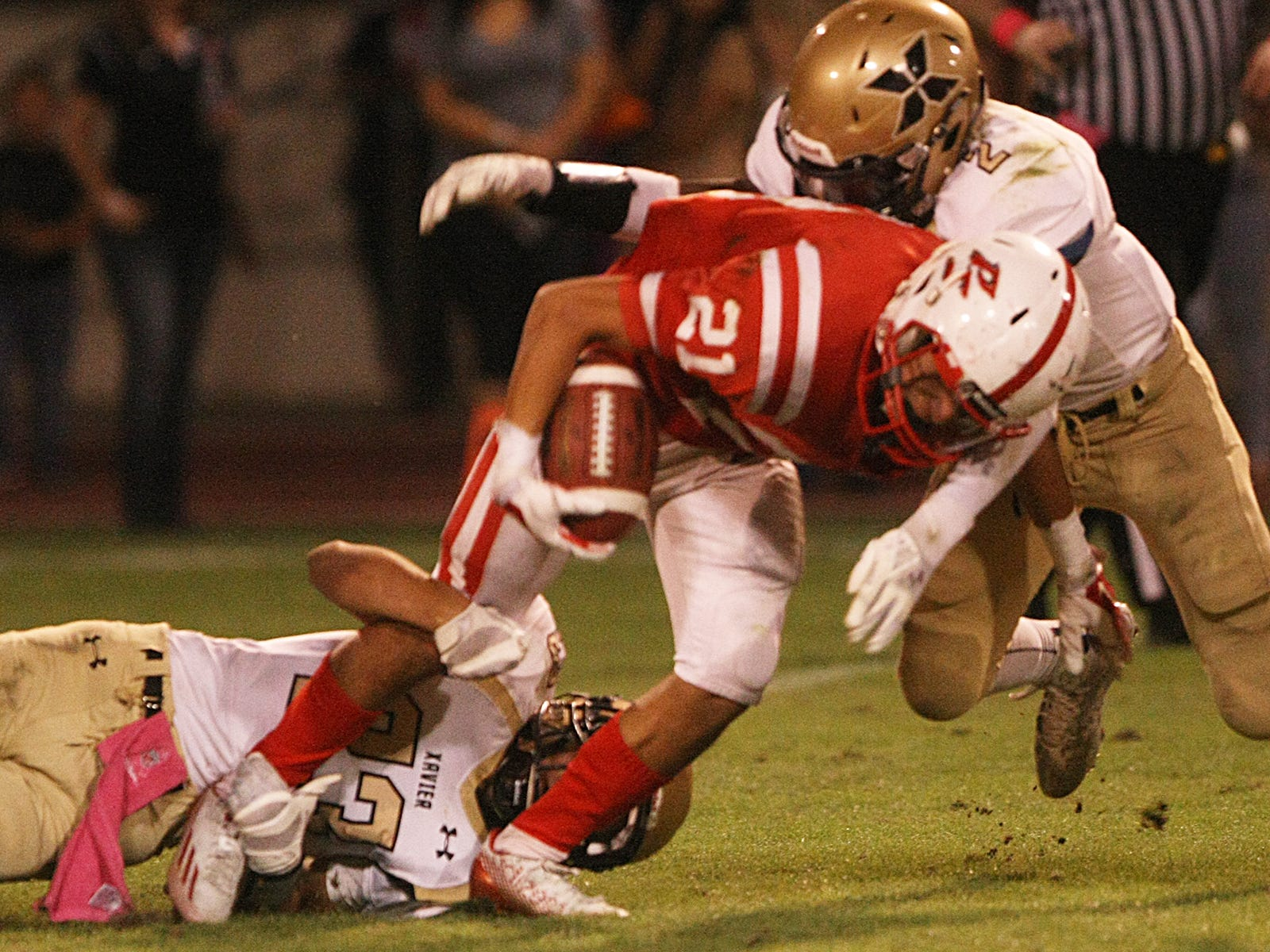 Saints defenders Mason Sarna (23) and Fisayo Omilana (2) combine to stop Indians ball carrier Randolph Mullen on Friday. The Indians won 42-7.