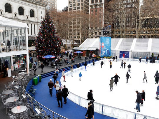 People ice skate at the Winter Village at Bryant Park
