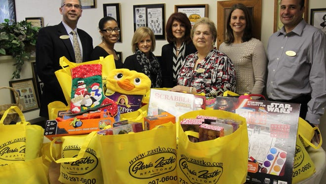 Gloria Zastko Realtors does many charity collections during the holidays. In addition to the Thanksgiving food drive,  Gloria Zastko Realtors has collected gifts for the Women Aware Holiday Gift Shop, led by Maria Reyolds, third from the right.