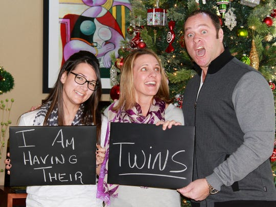 Summer Marnin, left, is the gestational carrier for Stacey Baker, center, and her husband, Chad. The Marnin and Baker families during the December 2013 holidays posed for announcement photos by the Christmas tree - Marnin was pregnant with the Bakers' twins.