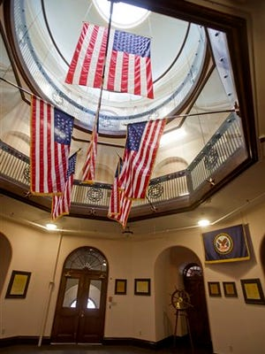 In this photo taken April 13, 2015, American flags hang in the grand rotunda entry to Battle Mountain Sanitarium, a historic VA hospital in Hot Springs, S.D. Completed in 1907, much of the hospital campus has changed little since it opened to treat veterans of the Civil War and Spanish American War. But this long tradition of treating the nation's veterans at this National Historic Landmark could soon end with Veterans Affairs officials proposing to shutter the campus. (AP Photo/Kristina Barker)