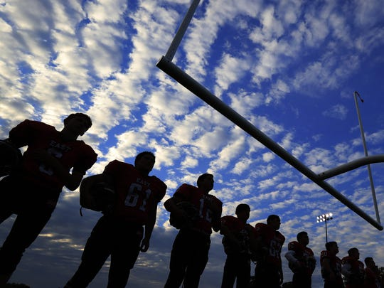Green Bay East players line up for the national anthem before a Bay Conference high school football game against Seymour on Friday at City Stadium in Green Bay.