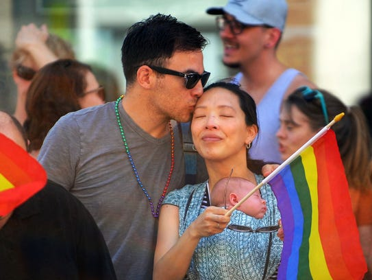 Carlos Juarez kisses his wife Rebecca who holds their