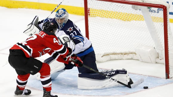New Jersey Devils center John Quenneville (42) is unable to score on Winnipeg Jets goalie Connor Hellebuyck (37) during a shootout of an NHL game, Tuesday, March 28, 2017, in Newark, N.J. The Jets won 4-3. (AP Photo/Julio Cortez)