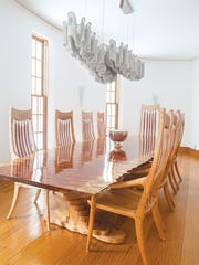 Light color choices enlarge the kitchen and eating area, but nearly blonde wood moldings and window and door frames bring warmth to those spaces. The dining room table is from a slab of waterfall bubinga and made by Scott Sober of Cyma Furniture Design.