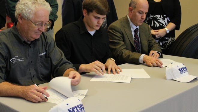 Keith Hamilton, left to right, Jacob Dean and Ahad Nasab sign agreements for Dean to transfer to MTSU and become a mechatronics intern at Bridgestone's La Vergne plant. Dean is the first student in the nation to successfully transfer mechatronics credits from high school to community college and finally to a university.