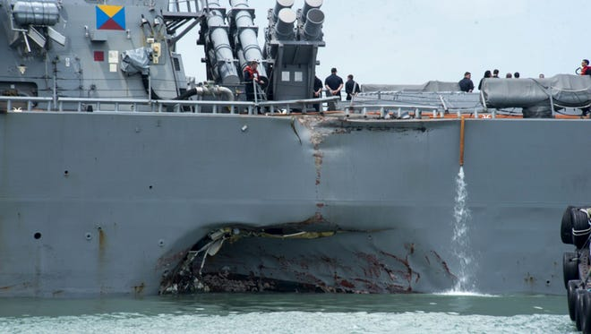 Damage to the side of the USS John S. McCain is visible after an early morning collision Monday with a tanker ship.