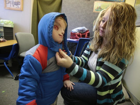 Lacey Buchanan closes the coat on her son, Christian.