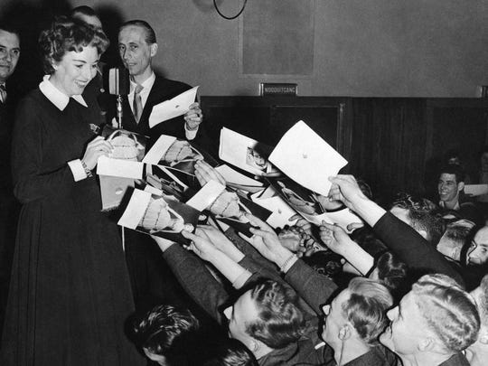 Dutch soldiers and sailors cluster around Vera Lynn for autographs after she performed in the Netherlands on Dec. 9, 1954.
