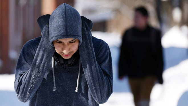 John Solares, 14, of the City of Poughkeepsie, tries to keep his ears warm as he walks along Holmes Street on Monday in the City of Poughkeepsie. Feb. 16, 2015