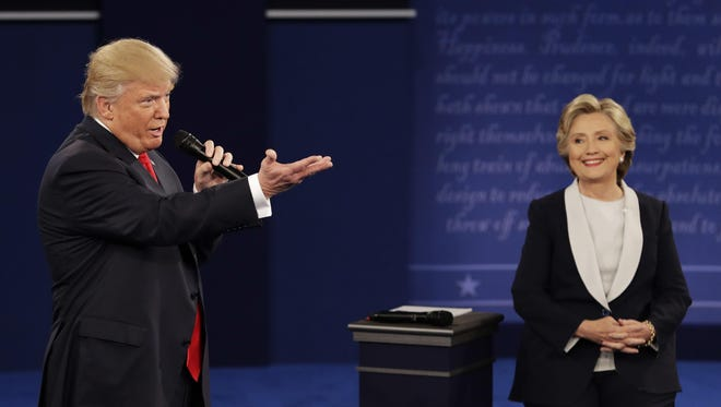 Republican presidential nominee Donald Trump speaks with Democratic presidential nominee Hillary Clinton during the second presidential debate at Washington University in St. Louis on Sunday.