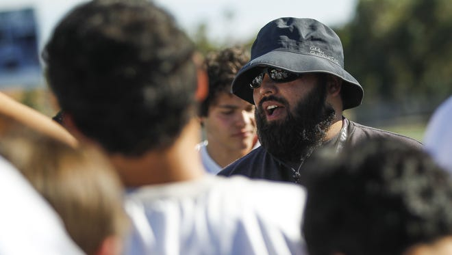 Coach Jose Lucero talks with his team the North Canyon High School football team practices on Wednesday, May 11, 2016, at North Canyon High School in Phoenix, Ariz.