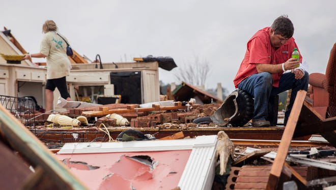 Jeff Bullard sits in what used to be the foyer of his home as his daughter, Jenny Bullard, looks through debris at their home that was damaged by a tornado, Sunday, Jan. 22, 2017, in Adel, Ga. Gov. Nathan Deal declared a state of emergency in several counties, including Cook, that have suffered deaths, injuries and severe damage from weekend storms. (AP Photo/Branden Camp)