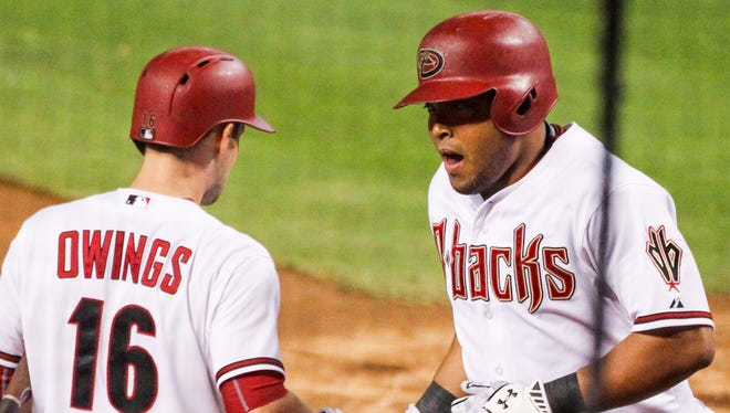 Arizona Diamondbacks outfielder Yasmany Tomas (24) high-fives second baseman Chris Owings (16) after hitting a home run in the 4th inning at Chase Field in Phoenix, AZ, on Monday, August 10, 2015.