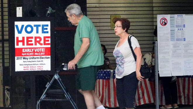 Mont and Flora Fyffe walk out of the early voting station at Bassett Place on Tuesday during the last day of early voting for the Saturday election.