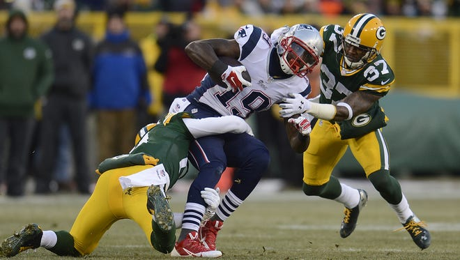 Green Bay Packers safety Ha Ha Clinton-Dix (21) and cornerback Sam Shields (37) tackle New England Patriots receiver Brandon LaFell (19) during Sunday's game at Lambeau Field.