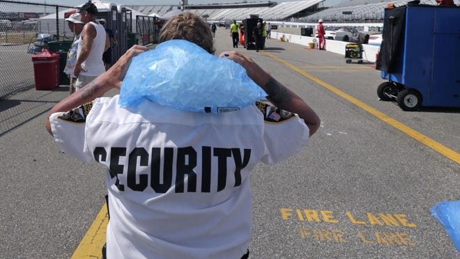 Patty Patterson, a track security officer at New Hampshire Motor Speedway in Loudon, carries a bag of ice on her shoulders as she walks back to her post during a NASCAR Cup Series auto race practice in July.