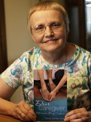Sharon Vander Waal of Oostburg, poses with her book about being a caregiver Thursday July 31, 2014 at her home.