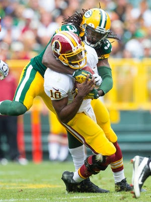 Washington Redskins quarterback Robert Griffin III (10) is sacked by Green Bay Packers cornerback Davon House (31) during the second quarter at Lambeau Field.