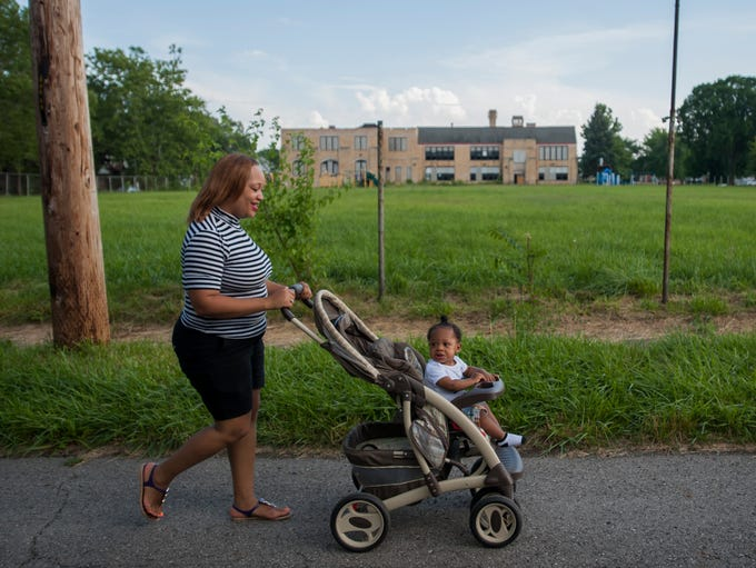 Alita Moore and her 1-year-old son Malachi stroll down Grixdale  to a neighborhood park.  An MSU graduate in communications, Alita moved back to Detroit last July after working in Atlanta and Chicago.  Currently she is a business customer care representative for AT&T and living with her mother in north central Detroit.