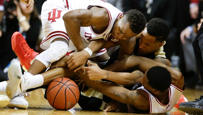 Indiana guard Yogi Ferrell (11), top, and forward Troy Williams (5), bottom right, fight for a loose ball with Purdue forward Vince Edwards during the second half Saturday.