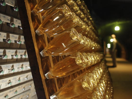 Bottles of sparkling wine sit on a rack inside a cave at Schramsberg Vineyards and Cellars in Calistoga, Calif.