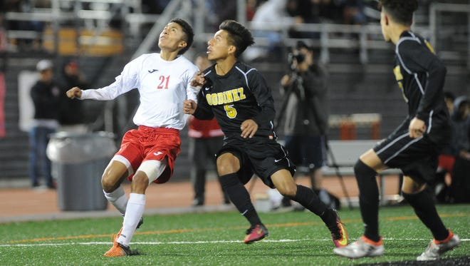 Hueneme's JD Martinez, left, fights for control of the ball against Godinez's Oscar Salas during Tuesday night's Division 2 semifinal game at Ventura College.