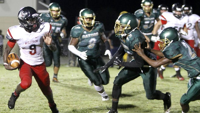 South ball carrier E'Quan Dorris eyes a trio of Island Coast defenders at the Island Coast-South Fort Myers football game Friday in Cape Coral.
