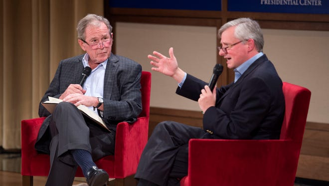 Former President George W. Bush, left, listens to Pulitzer Prize winning author Jon Meacham, right, talk about his biography of Bush's father, former President George H. W. Bush, Sunday, Nov. 8, 2015 at the George W. Bush Presidential Center in Dallas.