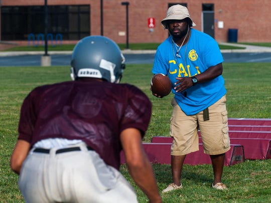 Snow Hill head coach Timothy Richo works with his running