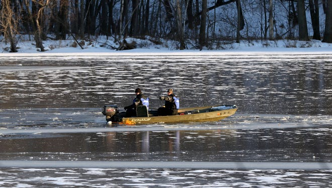 Wisconsin Department of Natural Resources Wardens cut through ice on the Wisconsin River in Nekoosa while searching after a 9-1-1 caller reported someone jumping from the Highway 73 bridge on February 9, 2016.