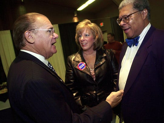 In this 2004 LSJ file photo, Ingham County Prosecutor Stuart Dunnings III, right,  and Ingham County Sheriff Gene Wrigglesworth, left, speak about the election with supporter Ann Bitzer of Grand Ledge.