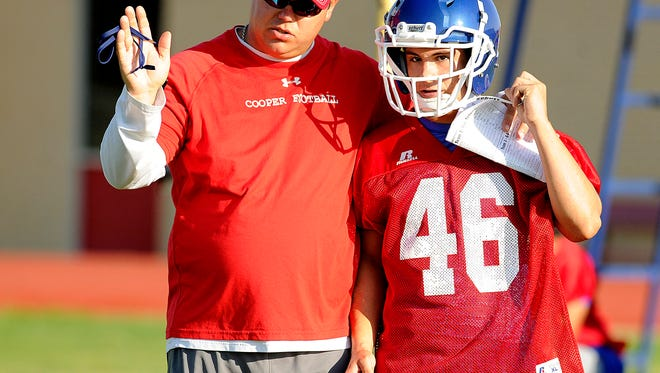 Cooper head coach Todd Moebes gives instruction to a player during the Cougars' first practice of the 2013 season.