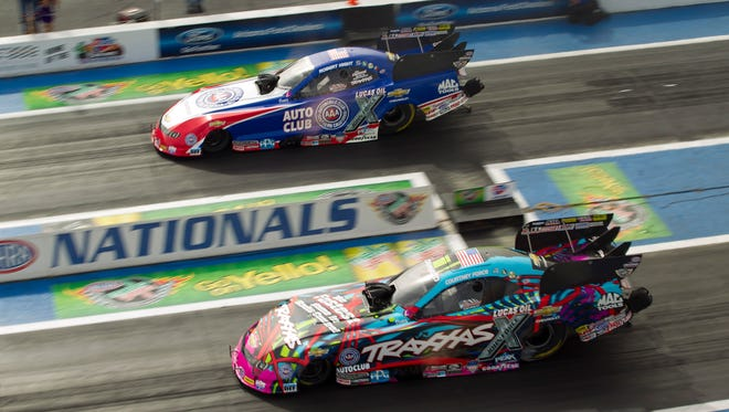 Courtney Force (bottom) driving the Traxxas Radio Control Cars Funny Car races Robert Hight driving the Automobile Club of Southern California Funny Car during the Funny Car third round of qualifying on the second day of action of the CARQUEST Auto Parts NHRA Nationals drag racing at Wild Horse Pass Motorsports Park in Chandler on Saturday, February 21, 2015.