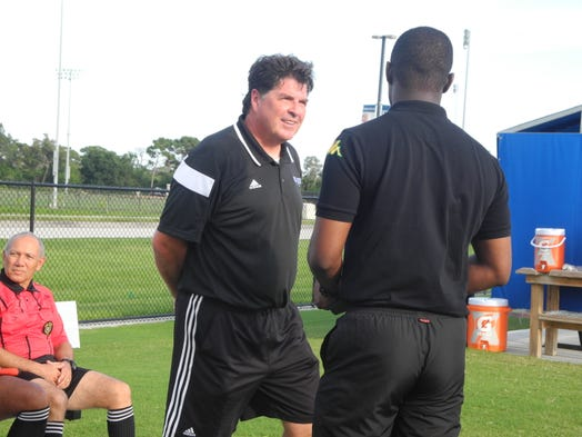 Eastern Florida head coach Jeff Carr speaks with a Jamaican national team coach before the match.