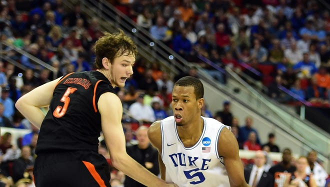 Mar 21, 2014; Raleigh, NC, USA; Duke Blue Devils forward Rodney Hood (5) drives to the basket against Mercer Bears forward Bud Thomas (5) in the second half of a men's college basketball game during the second round of the 2014 NCAA Tournament at PNC Arena. Mandatory Credit: Bob Donnan-USA TODAY Sports