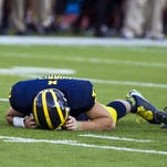 In this Sept. 27, 2014, photo, Michigan quarterback Shane Morris lays on the field after taking a hit. He was put back in the game and later determined to have a concussion.