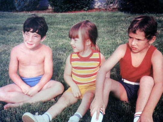 Elissa Gross, middle, sits with her adoptive brothers when she was a little girl.
