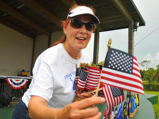 """Brevard celebrated the Fourth of July on Wednesday, keeping on eye on ominous clouds to the west. At Wickham Park, hundreds showed up for the Jesus is the Key Church & Ministries """"Lifting Up God & Country"""" celebration at the amphitheater. Patti Iheart-Bucci made sure each child had a small American flag."""