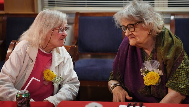 Martha Harrison, 104, talks to 101-year-old Blanca Higuera at a birthday party Woodcrest Health Care Center in New Milford hosted for them, and four other centenarians, on Friday.