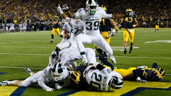 Michigan State Spartans defensive back Jalen Watts-Jackson (20) dives into the end zone for a game winning touchdown as the clock runs out in the fourth quarter against the Michigan Wolverines at Michigan Stadium. Michigan State 27-23.