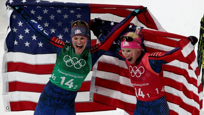 Jessie Diggins (left) and Kikkan Randall  celebrate winning a historic gold medal in the women's cross-country skiing team sprint freestyle final during the Pyeongchang 2018 Olympic Winter Games at Alpensia Cross-Country Centre on Feb. 21.